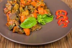 Gehackte Auberginen gedünstet mit anderem Gemüse auf braunem Tellercl stockfotografie