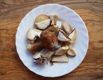 Gehackte gefrorene essbare Pilze des Boletus auf einer weißen Platte stockfotografie