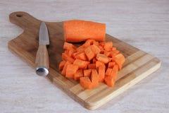 Gehackte Karotte auf einem hölzernen Schneidebrett Stockfotografie