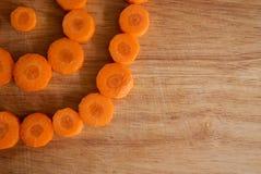 Gehackte Karottenkreise gegen Holz Stockfoto