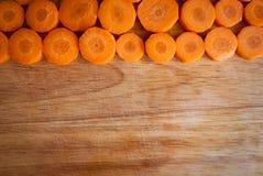Gehackte Karottenkreise gegen Holz Lizenzfreies Stockbild