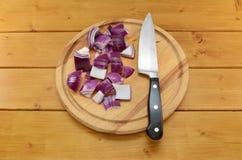 Gehackte rote Zwiebel mit einem Messer auf einem hackenden Brett Stockbilder
