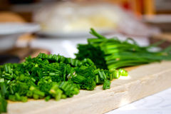 Gehackte Schnittlauche auf Brotschneidebrett in der Küche Lizenzfreie Stockbilder