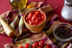 Gehackte Tomaten auf einem roten Hintergrund Vegetarische Nahrung stockfotografie