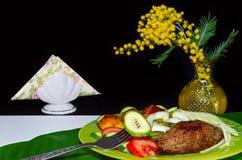 Gehackter Kebab vom Schweinefleisch mit Gemüse auf Tabelle und schwarzem Hintergrund Lizenzfreies Stockfoto