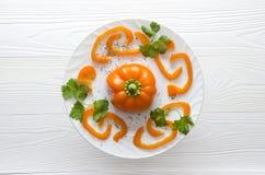 Gehackter orange Pfeffer auf Platte auf weißem hölzernem Hintergrund lizenzfreie stockbilder