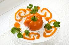 Gehackter orange Pfeffer auf runder weißer Platte lizenzfreie stockfotos