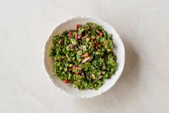 Gehackter Petersilien-Salat mit Tomaten und Zwiebeln in der keramischen Schüssel auf Marmoroberfläche stockfoto
