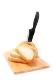 Gehacktes Brot mit Messer und hölzernem Vorstand Stockfotografie