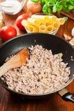 Gehakt met uien en knoflook in de pan wordt gebraden die Voorbereidingscannellonien Royalty-vrije Stock Foto