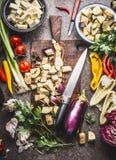 Gehakte aubergine op houten scherpe raad met mes en diverse vegetarische kokende ingrediënten voor het gezonde eten, hoogste meni Stock Foto
