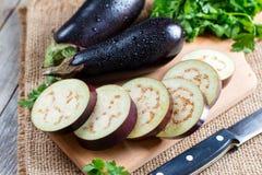 Gehakte aubergine op scherpe raad op houten achtergrond Royalty-vrije Stock Foto's