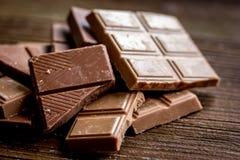 Gehakte chocoladestukken voor achtergrond van het dessert de donkere houten bureau Royalty-vrije Stock Afbeeldingen