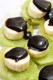 Gehakte die banaan op kiwi met chocoladesaus wordt gestapeld Stock Afbeeldingen