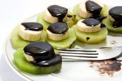 Gehakte die banaan op kiwi met chocoladesaus wordt gestapeld Stock Afbeelding