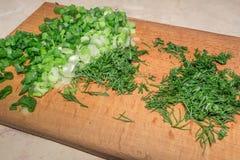 Gehakte groene uien en dille op een houten scherpe raad Stock Foto