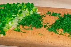 Gehakte groene uien en dille op een houten scherpe raad Stock Afbeeldingen