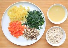 Gehakte groenten met soep en varkensvlees op witte plaat tegen houten raadsachtergrond stock foto's