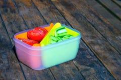 Gehakte komkommer en tomaat in plastic voedselcontainer op houten lijst Royalty-vrije Stock Fotografie