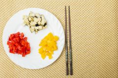 Gehakte rode en gele paprika en aubergine op witte plaat Chinese stokken voor het eten op rieten tafelkleed Het oosterse voedsel  Royalty-vrije Stock Fotografie
