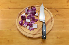 Gehakte rode ui met een mes op een hakbord Stock Afbeeldingen