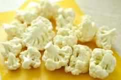 Gehakte stukken van bloemkool op gele scherpe raad Stock Foto