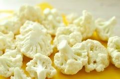 Gehakte stukken van bloemkool op gele scherpe raad Stock Afbeeldingen