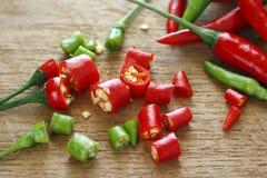 Gehakte verse rode en groene Spaanse pepers op houten hakkend blok Stock Afbeeldingen