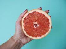 Gehalveerde grapefruit op blauwe achtergrond stock afbeeldingen