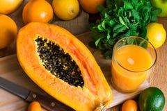 Gehalveerde rijpe papaja, vers gedrukt sap, verse munt, citrusvruchten, sinaasappelen, citroen, kalk, kumquat stock foto