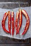 3 gehalveerde rode Spaanse pepers op een bakselblad Stock Foto