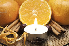 Gehalveerde sinaasappel, Kerstmiskruiden en kaars Stock Afbeeldingen