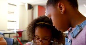 Gehandicapt Afrikaans Amerikaans schoolmeisje die bij bureau in klaslokaal op school 4 4k bestuderen stock video