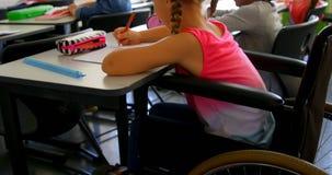 Gehandicapt Kaukasisch schoolmeisje die bij bureau in klaslokaal op school 4k bestuderen stock footage