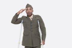 Gehandicapte Afrikaanse Amerikaanse militaire ambtenaar in eenvormige begroetingen over grijze achtergrond Stock Fotografie