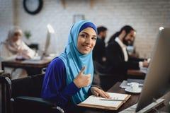 Gehandicapte Arabische vrouw in rolstoel die in bureau werken De vrouw geeft duimen op stock foto's