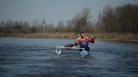 Gehandicapte atleet die op de rivier in een kano roeien Het roeien, canoeing, het paddelen Opleiding kayaking paraolympic sport stock footage