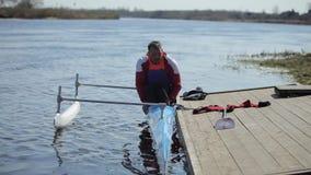 Gehandicapte atleet die van de boot bij de pijler proberen te krijgen Het roeien, canoeing, het paddelen Opleiding kayaking stock video