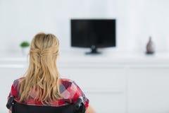 Gehandicapte hogere vrouw die op TV in woonkamer letten Royalty-vrije Stock Afbeeldingen