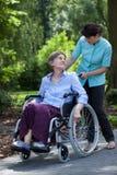 Gehandicapte hogere vrouw en verpleegster in park Stock Foto's
