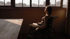 Gehandicapte jonge vrouw dichtbij het venster stock videobeelden
