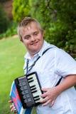 Gehandicapte jongen die de harmonika spelen. stock foto