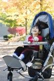 Gehandicapte jongen in medische rolstoel bij park Stock Afbeelding