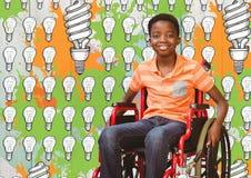 Gehandicapte jongen in rolstoel met gloeilampen en verftekeningen stock foto