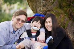 Gehandicapte jongen in rolstoel met vader en zuster stock afbeelding