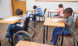 Gehandicapte leerling die bij bureau in klaslokaal schrijven Stock Foto's