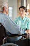 Gehandicapte mens die met verpleegster spreken Stock Afbeelding