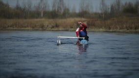 Gehandicapte mens die op de rivier in een kano roeien Het roeien, canoeing, het paddelen Opleiding kayaking paraolympic sport lan stock footage
