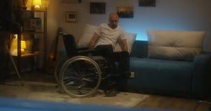Gehandicapte mens die van rolstoel aan bank overbrengen stock video
