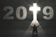 Gehandicapte mens met dwarssymbool en nummer 2019 royalty-vrije stock afbeeldingen